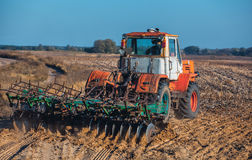 Stor, gammal härlig traktor som plogar jorden på fältet efter solrosor för skördhöstskörd arkivfoton