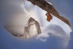 Stor glänsande kristall av genomskinlig kvarts i solljuset på närbilden för snövinterbakgrund arkivbild