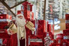 Stor gladlynt Santa Claus docka Santa Claus och många röda gåvaaskar med band och på skinande bakgrund Jul Arkivfoto