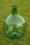 Stor glasflaska av vin som är tom, på bakgrund för grönt gräs Arkivfoton