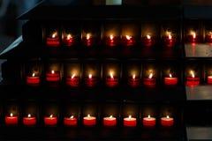 Stor grupp av bränningstearinljus på en svart bakgrund i churen Royaltyfria Foton