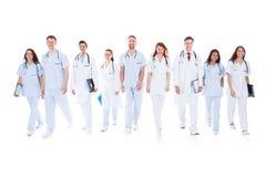 Stor grupp av doktorer och sjuksköterskor i likformig arkivbild