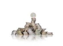 Stor grupp av krökta högar av mynt med ett euro överst arkivbilder