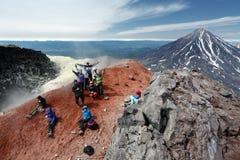 Stor grupp av lyckliga turister i toppmötekrater av den aktiva vulkan arkivfoton