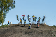 Stor grupp av ryttare på motorcyklar som hoppar över ett berg Royaltyfri Fotografi