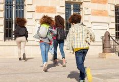 Stor grupp av ungar med ryggsäckar som kör till skolan royaltyfria bilder