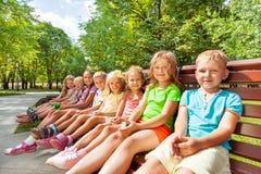 Stor grupp av ungar som sitter på bänken Royaltyfri Fotografi