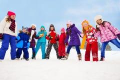 Stor grupp av ungar tillsammans på snödag Arkivfoton