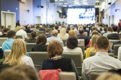 Stor grupp människor på en konferens Hållande ögonen på affärspresentation på en stor skärm framme Royaltyfri Foto
