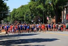 Stor grupp människorspring i Juli 4th ståtar, Saratoga Springs, New York, 2016 Royaltyfri Fotografi