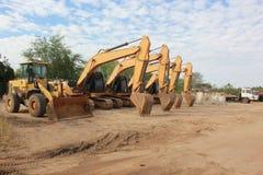 Stor gul grävskopa och annat konstruktionsmaskineri i arbeteutrymme arkivfoton