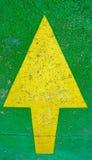 Stor gul pil som pekar upp med grön bakgrund royaltyfria bilder