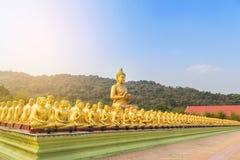 Stor guld- buddha staty och många små guld- buddha statyer som sitter i thai tempel Arkivbild