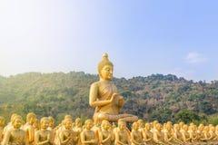 Stor guld- buddha staty och många små guld- buddha statyer som sitter i thai tempel Arkivbilder