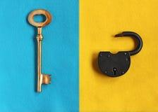 Stor guld- tangent på blå filt och den öppna hänglåset på gul filt Arkivfoto