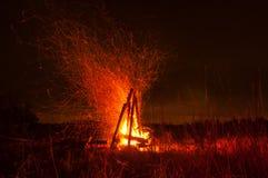 Stor härlig lägerbrand i nattskogen många ljusa gnistor flyger sammanlagt riktningar Royaltyfri Bild