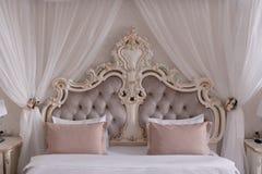 Stor härlig säng med kuddar i sovrumnärbilden royaltyfri foto