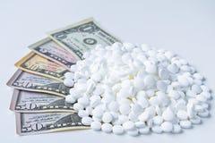 Stor hög av vita piller som sitter på räkningar för en dollar arkivfoto