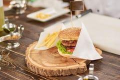 Stor hamburgare med fransmansmåfiskar i restaurang Arkivfoto