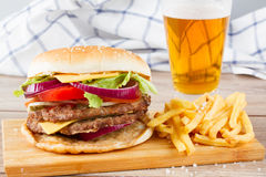Stor hamburgare med fransmansmåfiskar och öl arkivfoto