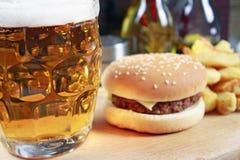 Stor hamburgare med fransmansmåfiskar och öl Royaltyfria Bilder