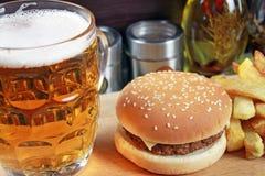 Stor hamburgare med fransmansmåfiskar och öl Royaltyfri Bild