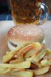 Stor hamburgare med fransmansmåfiskar och öl Fotografering för Bildbyråer