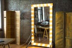 Stor hellång spegel i ett rum med en tegelstenvägg och ett fönster fotografering för bildbyråer