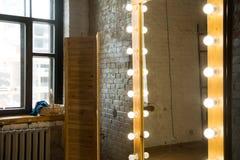 Stor hellång spegel i ett rum med en tegelstenvägg och ett fönster royaltyfri foto