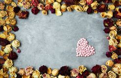 Stor hjärta av små dekorativa hjärtor i ram från torkade rosknoppar på grånar konkret bakgrund Arkivfoton