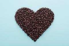 Stor hjärtaform som göras av kaffebönor på blått Arkivfoto