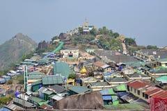 Stor husgemenskap över en liten kulle bak guld- vaggar (den Kyaiktiyo pagoden) Arkivbilder