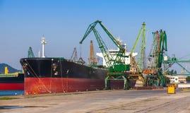 Stor industriell lastfartygpäfyllning i port Arkivbild