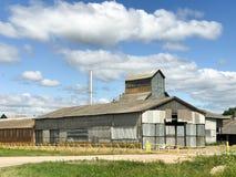 Stor jordbruks- jordbruks- lantgårdbyggnad med utrustning, hus, ladugårdar, spannmålsmagasin royaltyfri foto