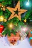 Stor julgåva med filialen och dekorativa stjärnor på ett träbräde Arkivfoto