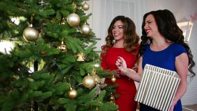 Stor julgran med guldbollar och blänkagirlander, flickvän nära julgranen som förbereder sig för det nytt stock video
