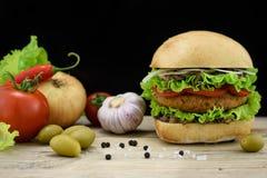 Stor kärnmjölk chiken hamburgaren med ingredienser på trätabellen, mörk bakgrund Arkivfoton