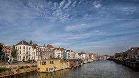 Stor kanal i Middelburg med husbåtar och traditionella holländska hus Arkivfoto