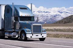 Stor klassisk halv lastbil på bergbakgrund Fotografering för Bildbyråer