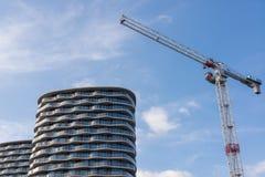 Stor konstruktionskran bredvid moderna lägenheter för höghus arkivfoton