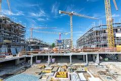 Stor konstruktionsplats med fundament, materialet till byggnadsställning och kranar royaltyfria foton