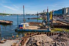 Stor konstruktionsplats med kranar på vattnets kant med att arbeta för folk fotografering för bildbyråer