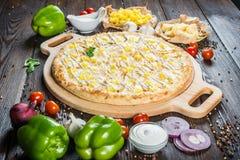 Stor krämig pizza med vit sås, höna och ananors på a royaltyfria bilder