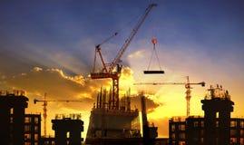 Stor kran- och byggnadskonstruktion mot härlig dunkel himmel