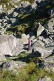 Stor kullersten och liten kvinna i berg Arkivfoto