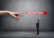 Stor kvinnlig arm som pekar på den röda pilen med & x27; you& x27; beträffande avfyrad words& x27; över småföretagare Royaltyfri Bild