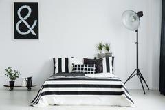 Stor lampa nära till jättestor säng Arkivfoton