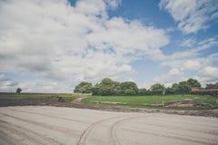 Stor lantlig gård med spår i sand Arkivfoto