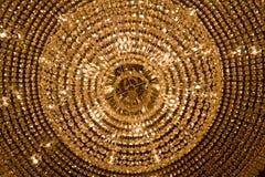 Stor ljuskrona med gula kristaller Arkivbild