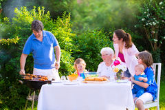 Stor lycklig familj som tycker om bbq-gallret i trädgården Arkivbild
